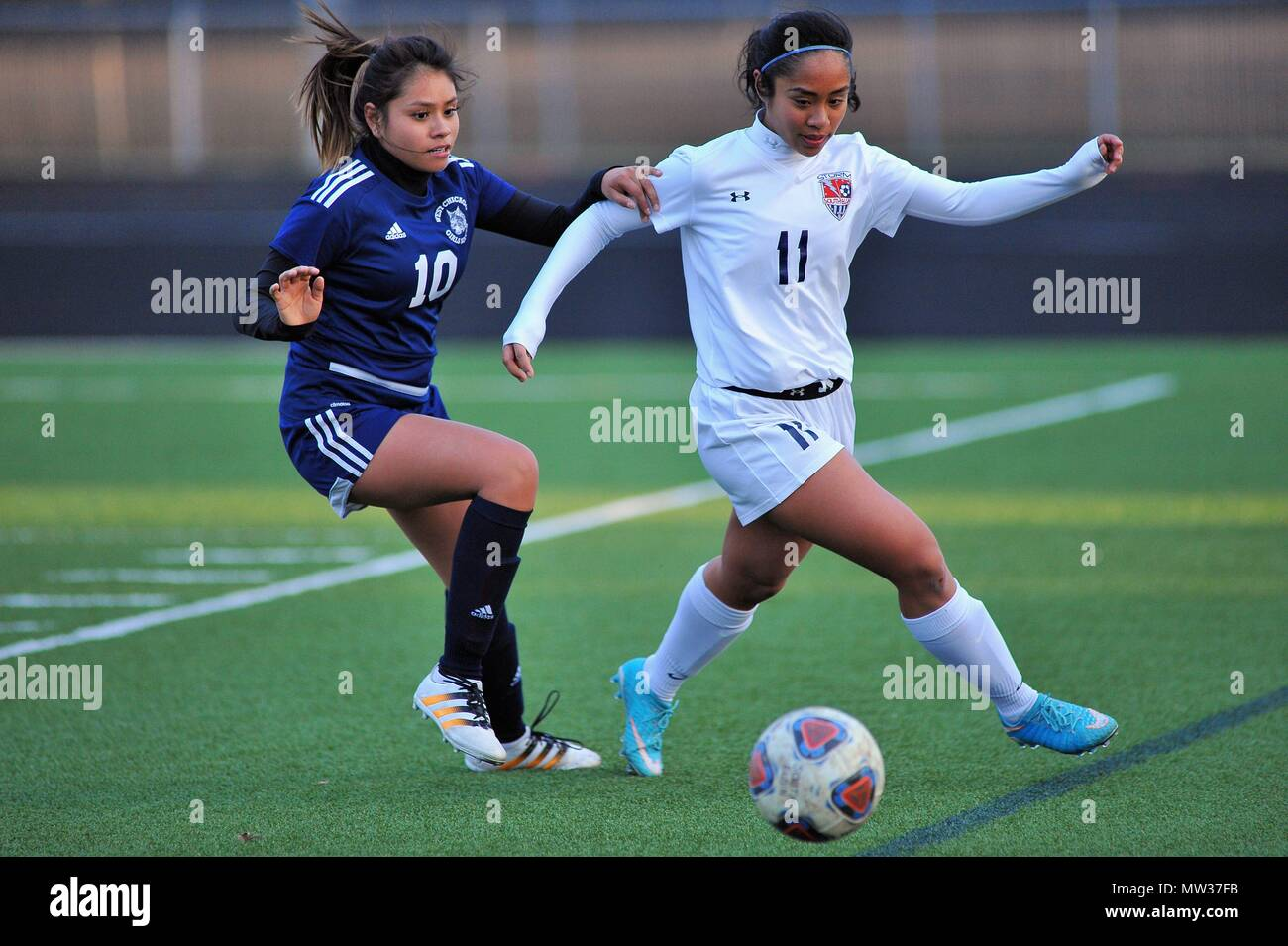Players battling for possession of the ball along a sideline. USA. - Stock Image