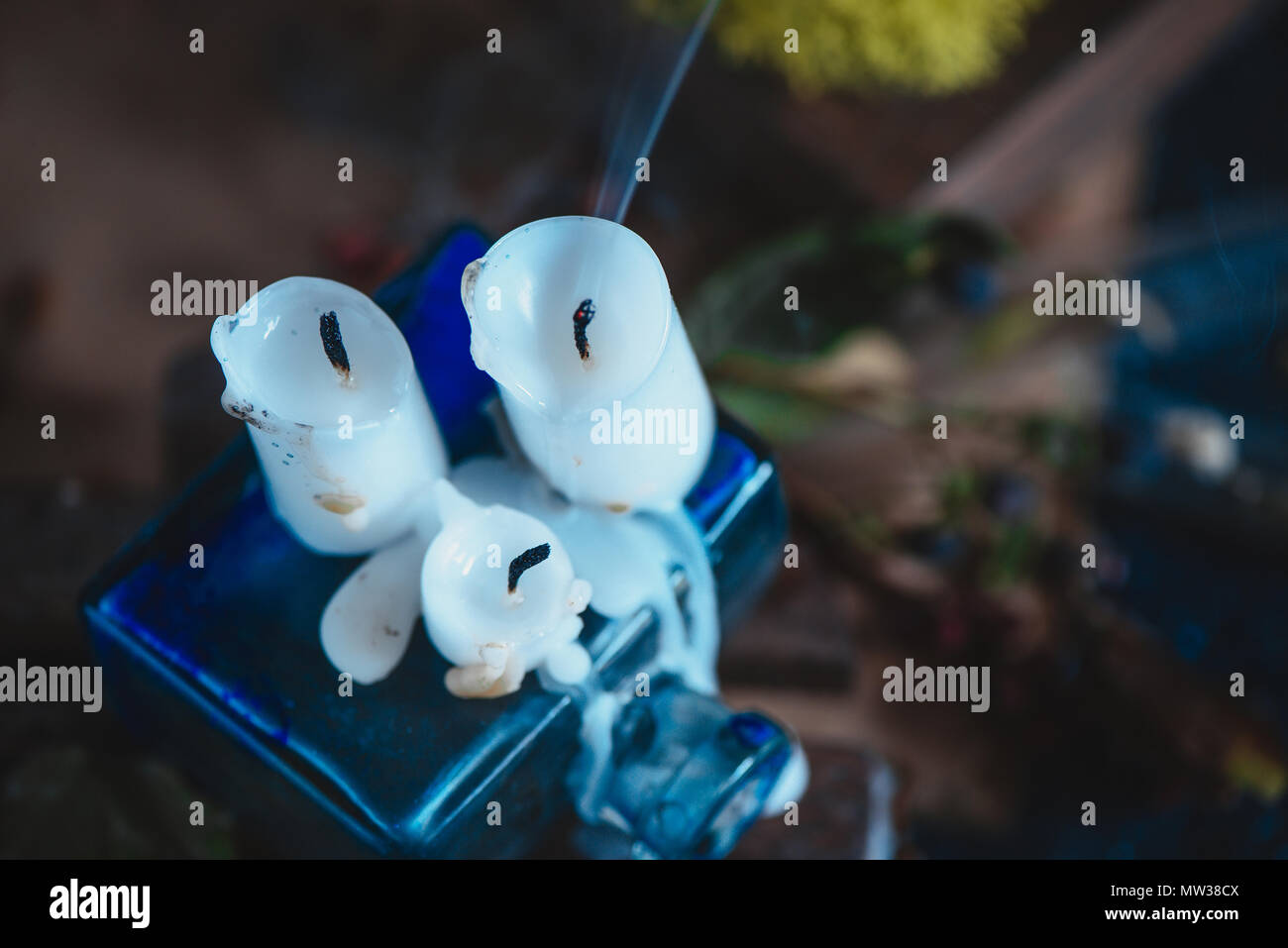 Extinguished white wax candles in a magical still life with potions and moss. Occult concept with copy space. - Stock Image