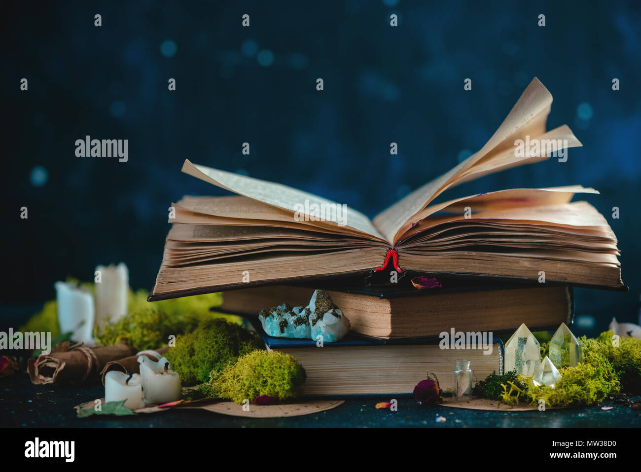Open book with candles, crystals, and moss. Reading fantasy concept with copy space. Magical still life on a dark background with occult equipment. - Stock Image