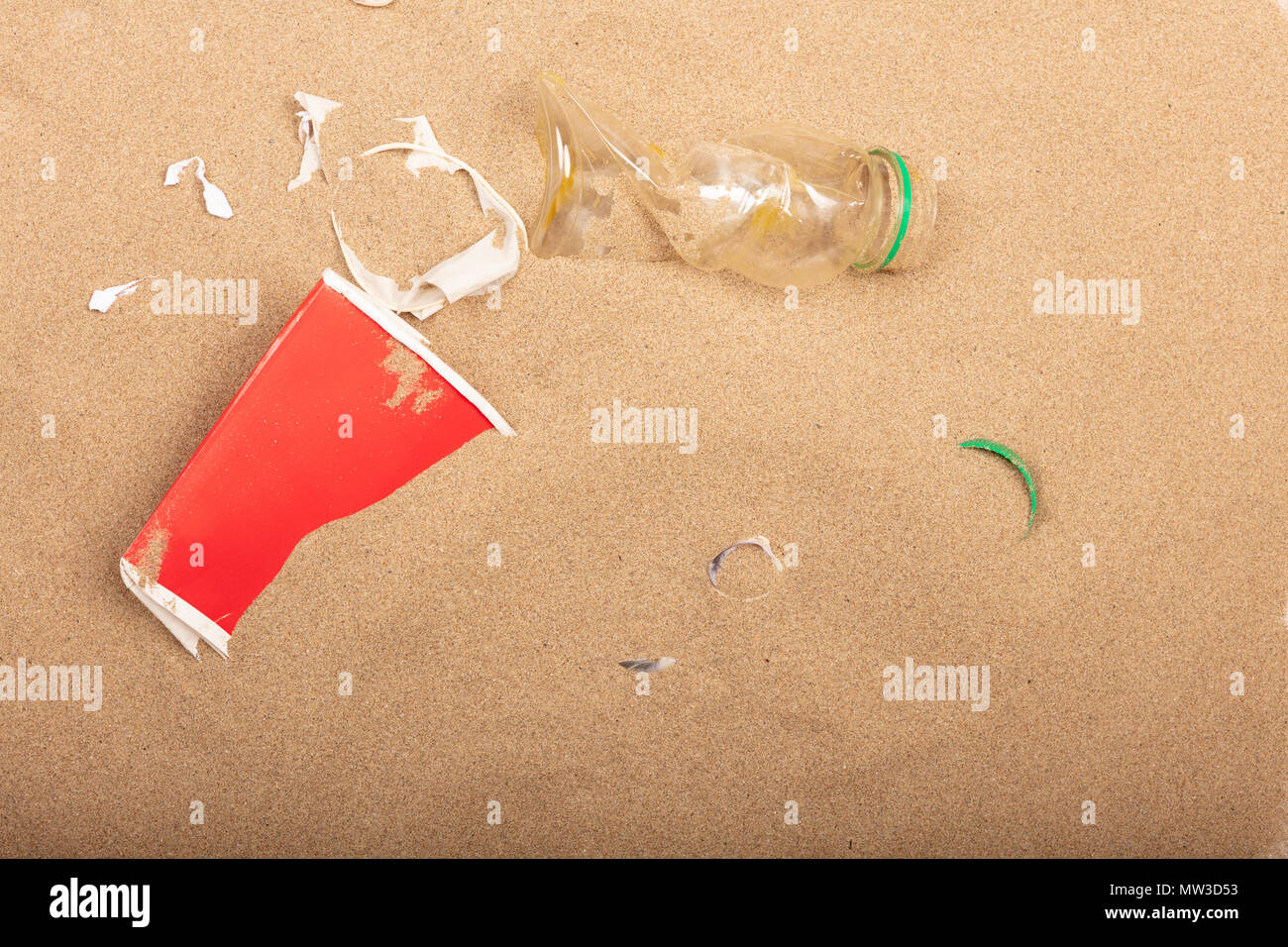 Waste plastic bottles and other types of wastes are lying on the sand of  a beach - Stock Image