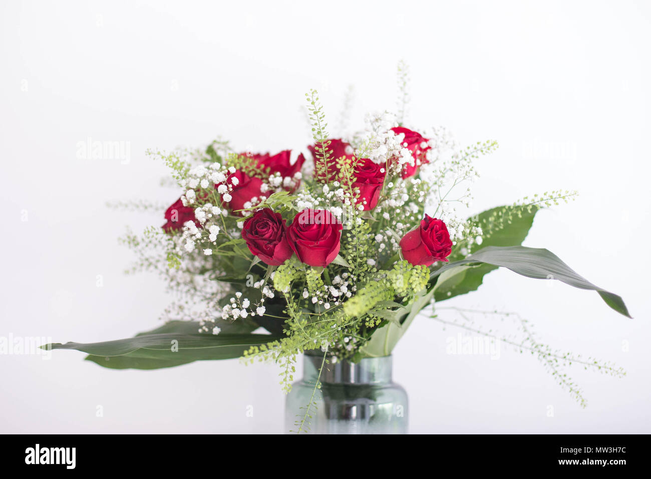 Beautiful Roses Bouquet In A Vase With Green Leaves And White