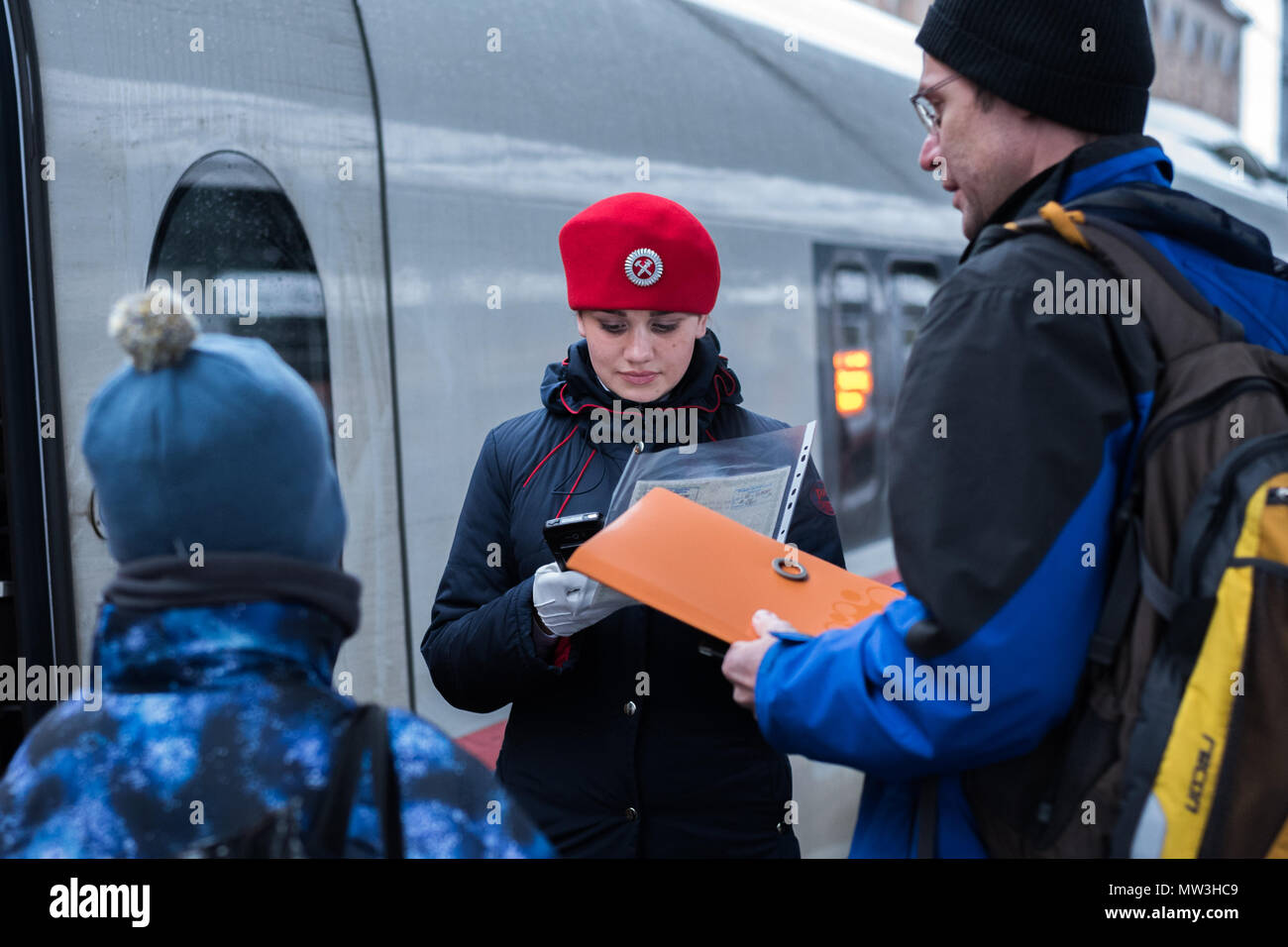 Saint Petersburg, Russia: a train conductor in a red beret of a Sapsan express train checks in a passenger with a child using electronic device. Stock Photo