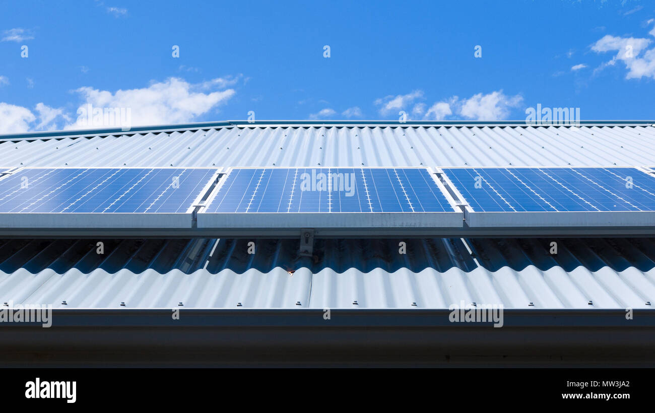 Solar panels on the roof of a house on a bright, sunny day. - Stock Image