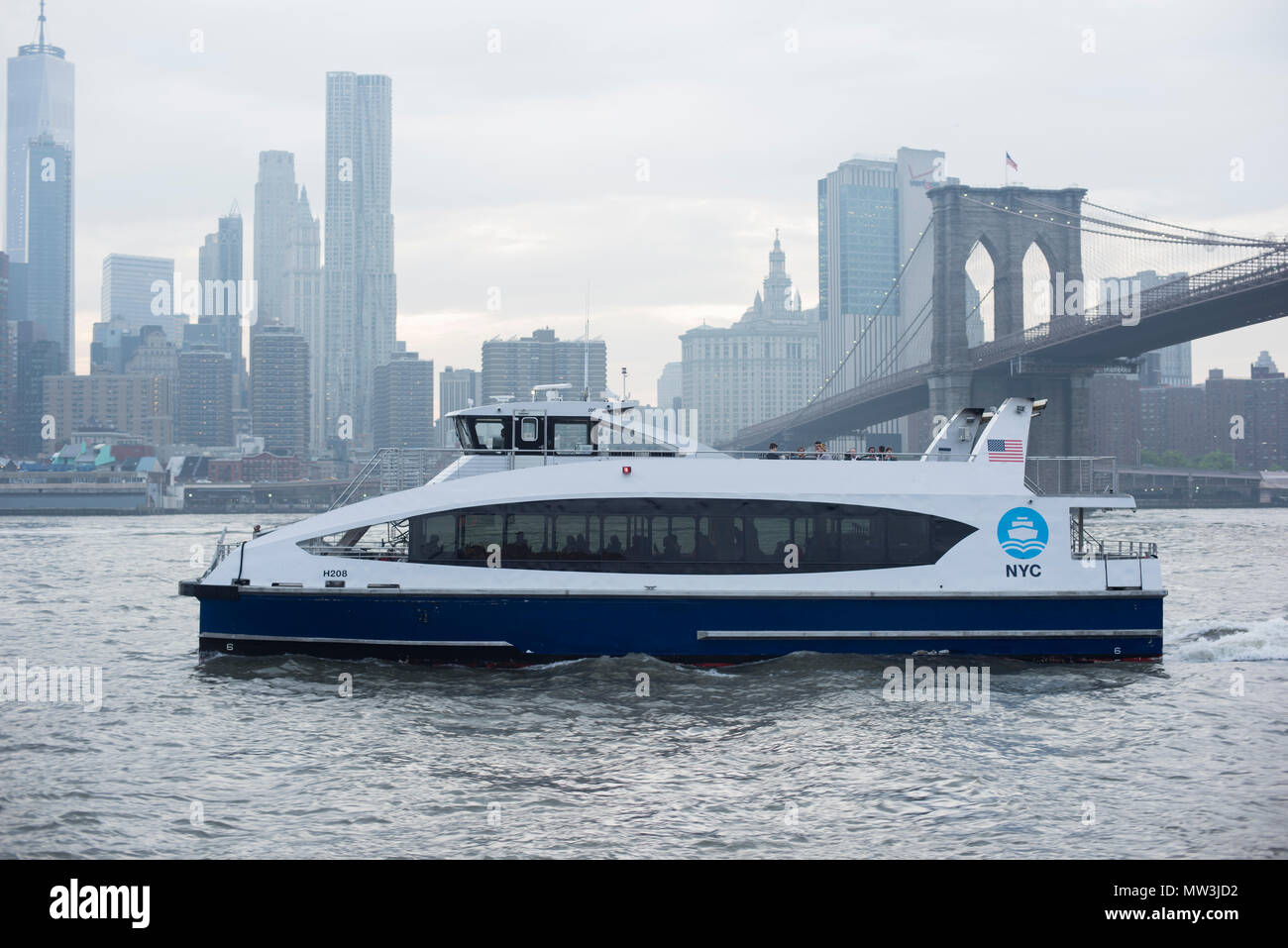 NYC Ferry and Brooklyn Bridge on a Cloudy Day Stock Photo