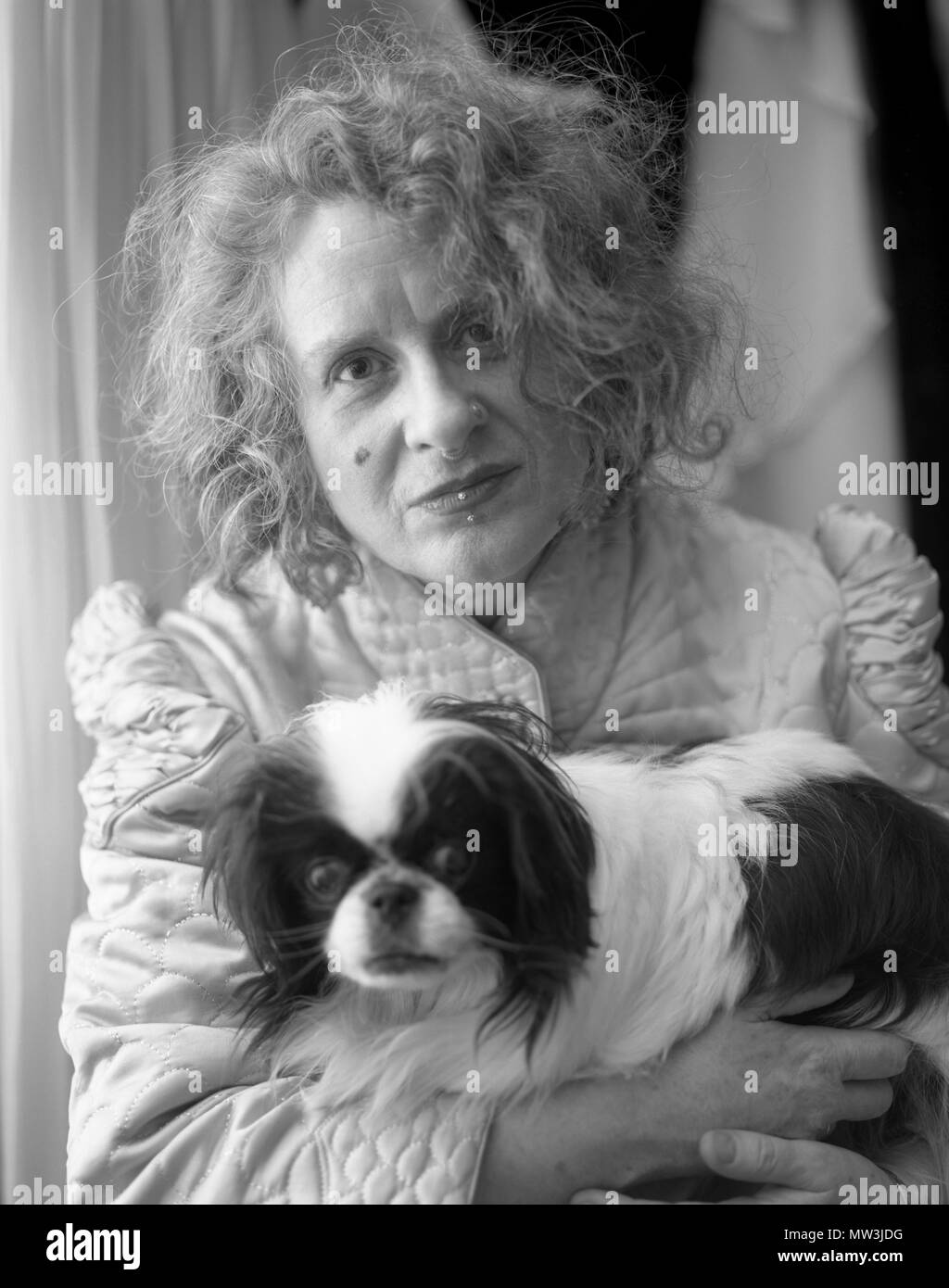 Black and white portrait of woman with facial piercings and frizzy hair holding her Japanese Chin rescue dog. Stock Photo