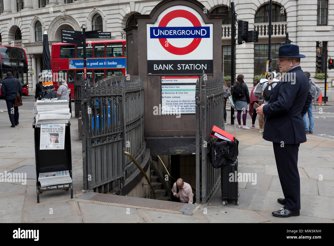 A businessman uses his mobile phone and another emerges from Bank Underground Station at the corner of King William Street in the City of London, on 30th May 2018, in London, England. Stock Photo