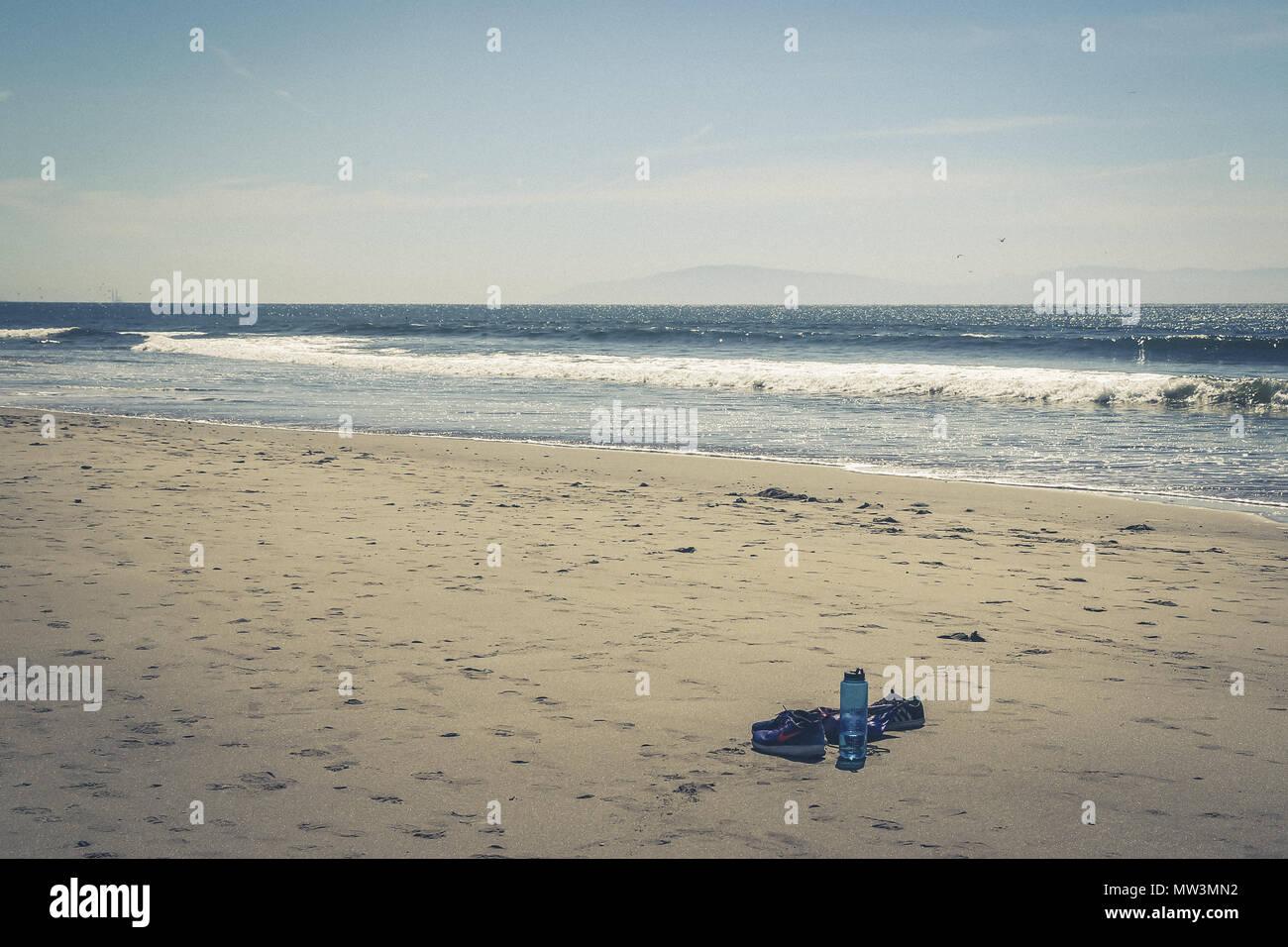 Water bottle and shoes abandoned on santa cruz beach - Stock Image