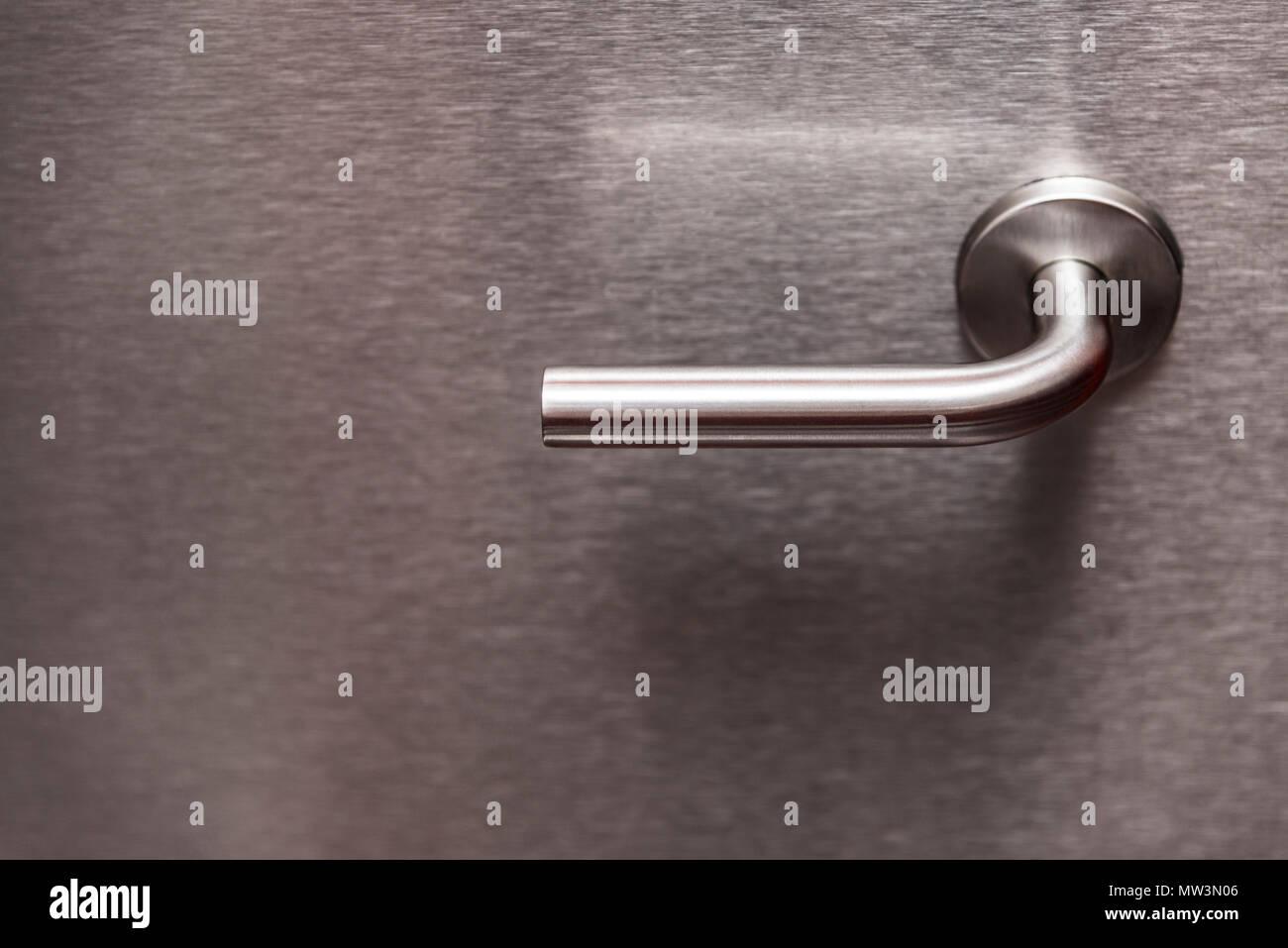 Metal handle on metal door - Stock Image