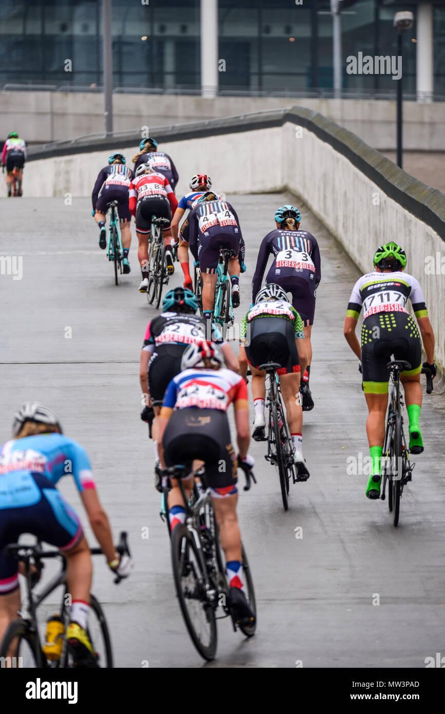 Female riders racing in the elite women's 2018 OVO Energy Tour Series cycle race at Wembley, London, UK, climbing towards stadium. Round 7 bike race. - Stock Image