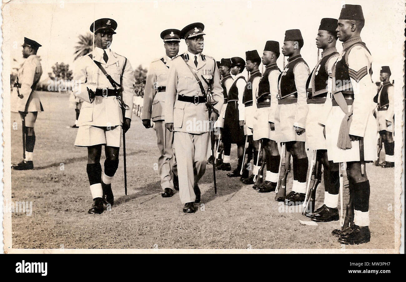 . English: He rapidly rose through the ranks and was promoted to an Assistant Superintendent of Police in 1949, one of the only four Africans to attain that rank at a period when nationalistic fervour was at its peak and the Colonial Government viewed each Nigerian with suspicion. He attended several courses in the United Kingdom including Police College Ryton –on-Dunsome in 1956, and proceeded to Police College Kincardine Scotland in 1960. 21 September 2014, 07:22:23. Wole Soyinka 455 Olufunwa Inspecting A Parade Stock Photo