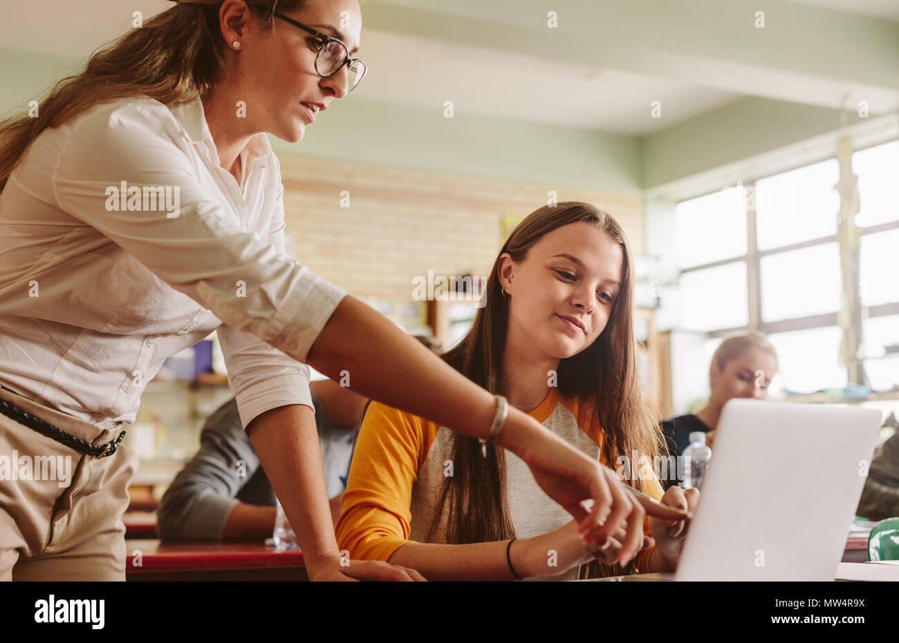 Teacher helping student in classroom. Lecturer pointing at laptop screen and showing something to female student. - Stock Image