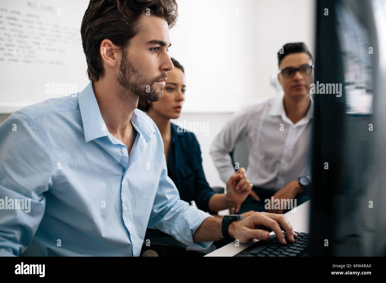 Software developers sitting in front of computer and working in office. Two men and a woman looking at computer and developing applications in office. - Stock Image