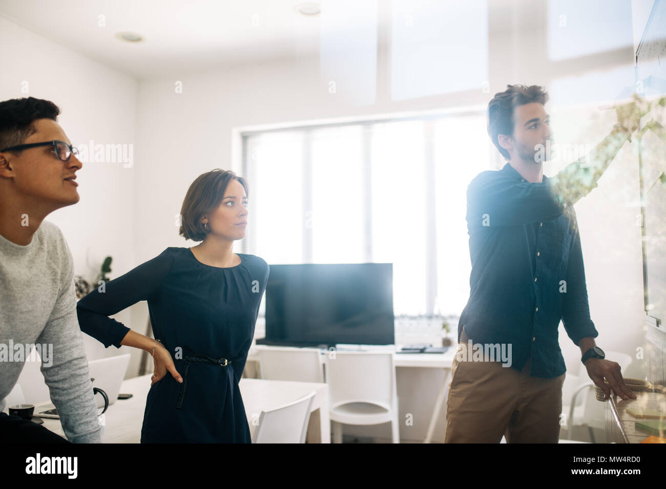 Man writing on board in the meeting room while his colleagues look on. Application developers in the board room discussing ideas and work. - Stock Image