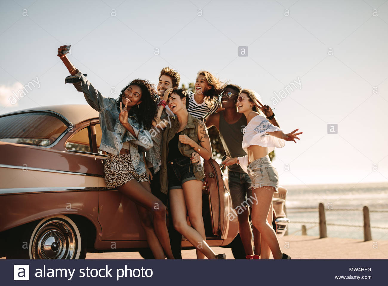 Diverse friends on road trip taking selfie with mobile phone. Group of men and women taking self portrait outdoors by the car. - Stock Image