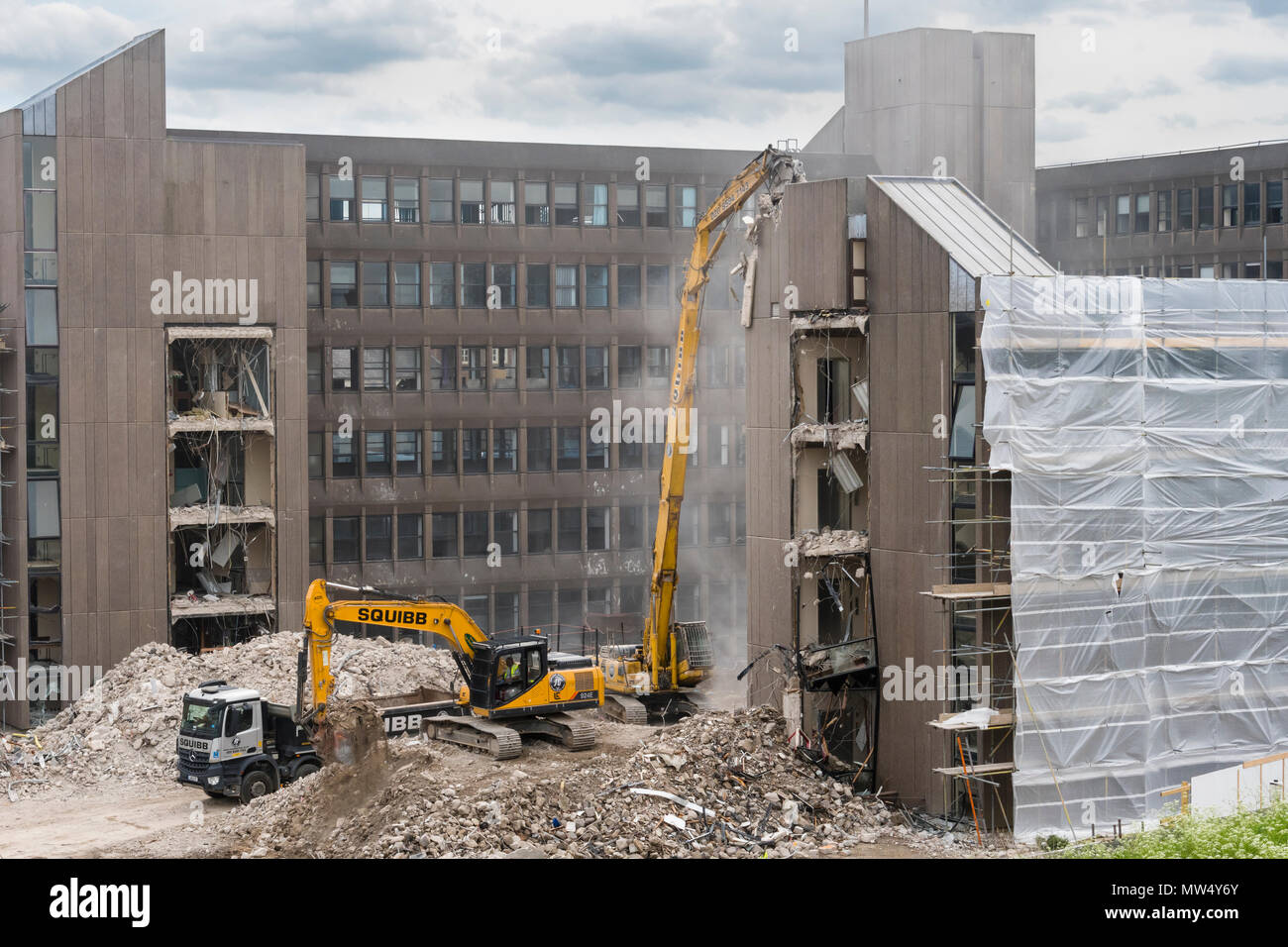 High view of demolition site with rubble, heavy machinery (excavators) working & demolishing empty office building - Hudson House  York, England, UK. - Stock Image