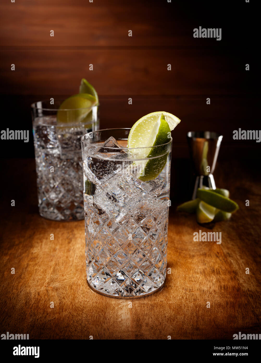 Spotlight on two crystal glasses full of the Gin and tonic cocktail, with a lime garnish, shot on a antique wooden table top. - Stock Image
