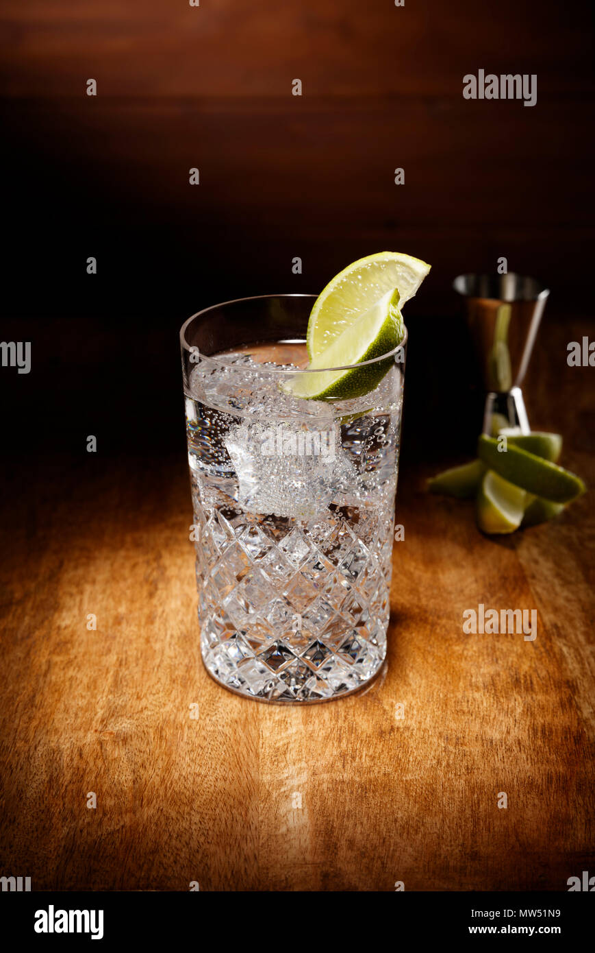 Spotlight on a crystal glasses full of the Gin and tonic cocktail, with a lime garnish, shot on a antique wooden table top. - Stock Image