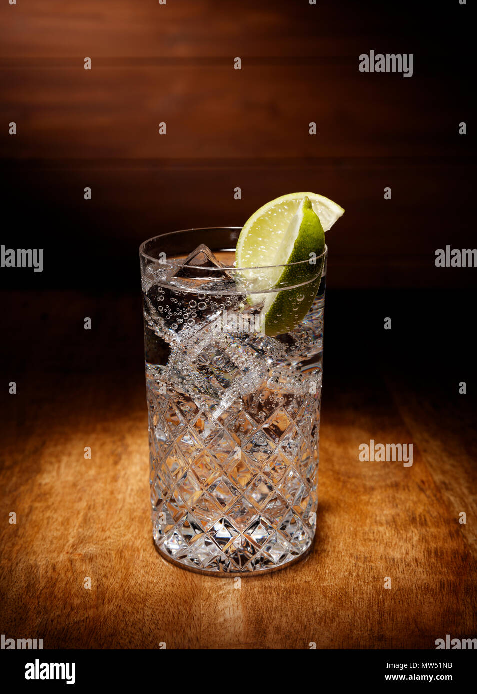 Spotlight on a single glasses full of the Gin and tonic cocktail, with a lime garnish, shot on a antique wooden table top. - Stock Image