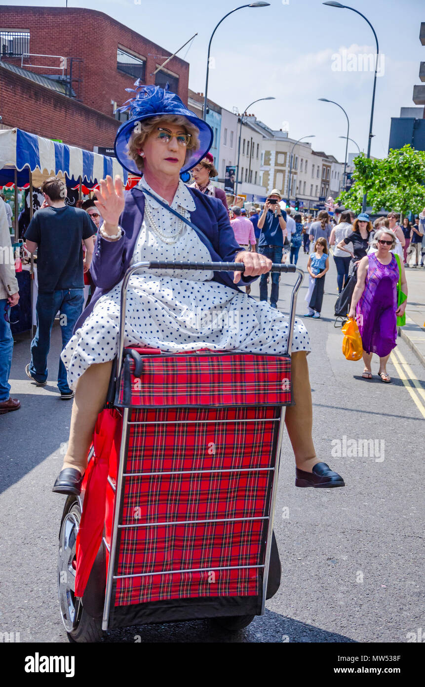 A man dressed up as an old woman riding a shopping trolley is actually a street performer entertaining crowds at a Hammersmith & Fulham Spring Market - Stock Image
