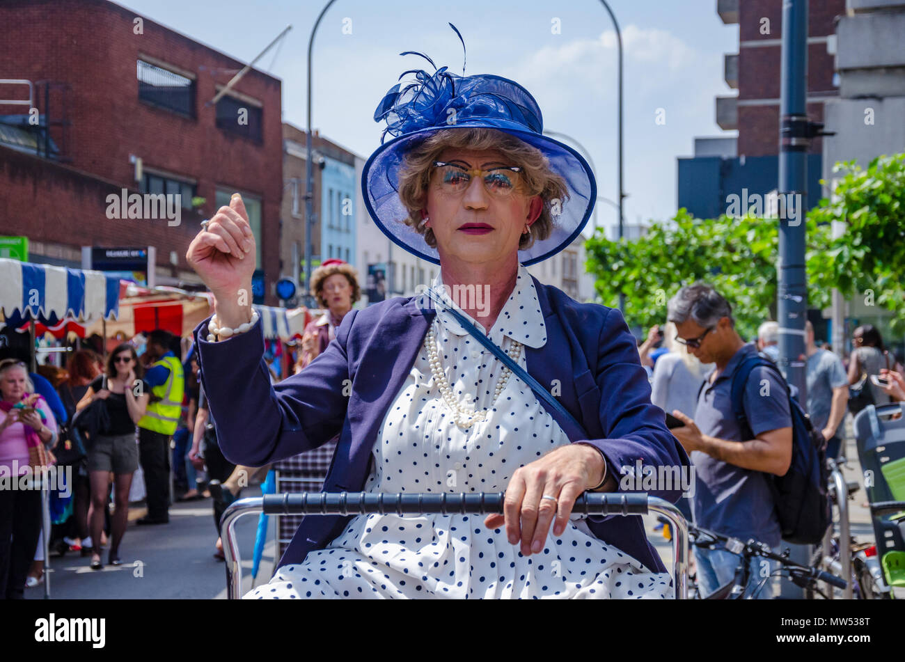 A man dressed up as an old woman riding a shopping trolley is actually a street performer entertaining crowds at a Hammersmith & Fulham Spring Market Stock Photo