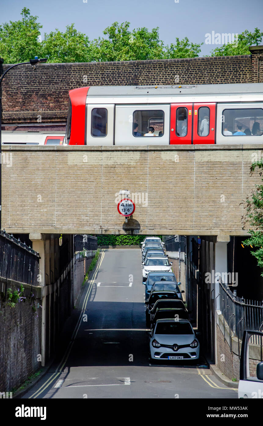 London Underground trains pass over a bridge over Leamore Street in Hammersmith, London. - Stock Image