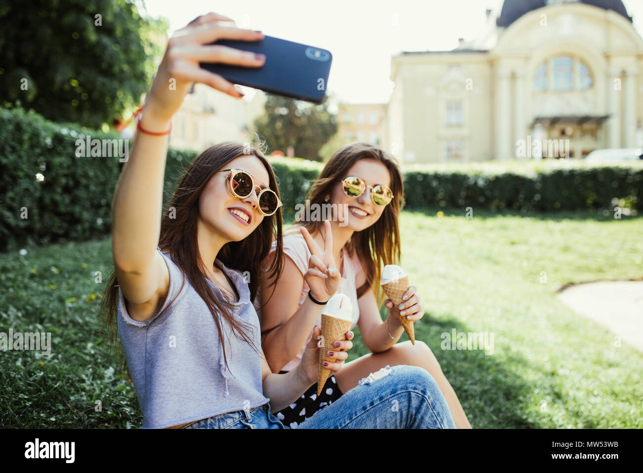 Two women friends take selfie while eating ice cream near river at sunset in summer - Stock Image