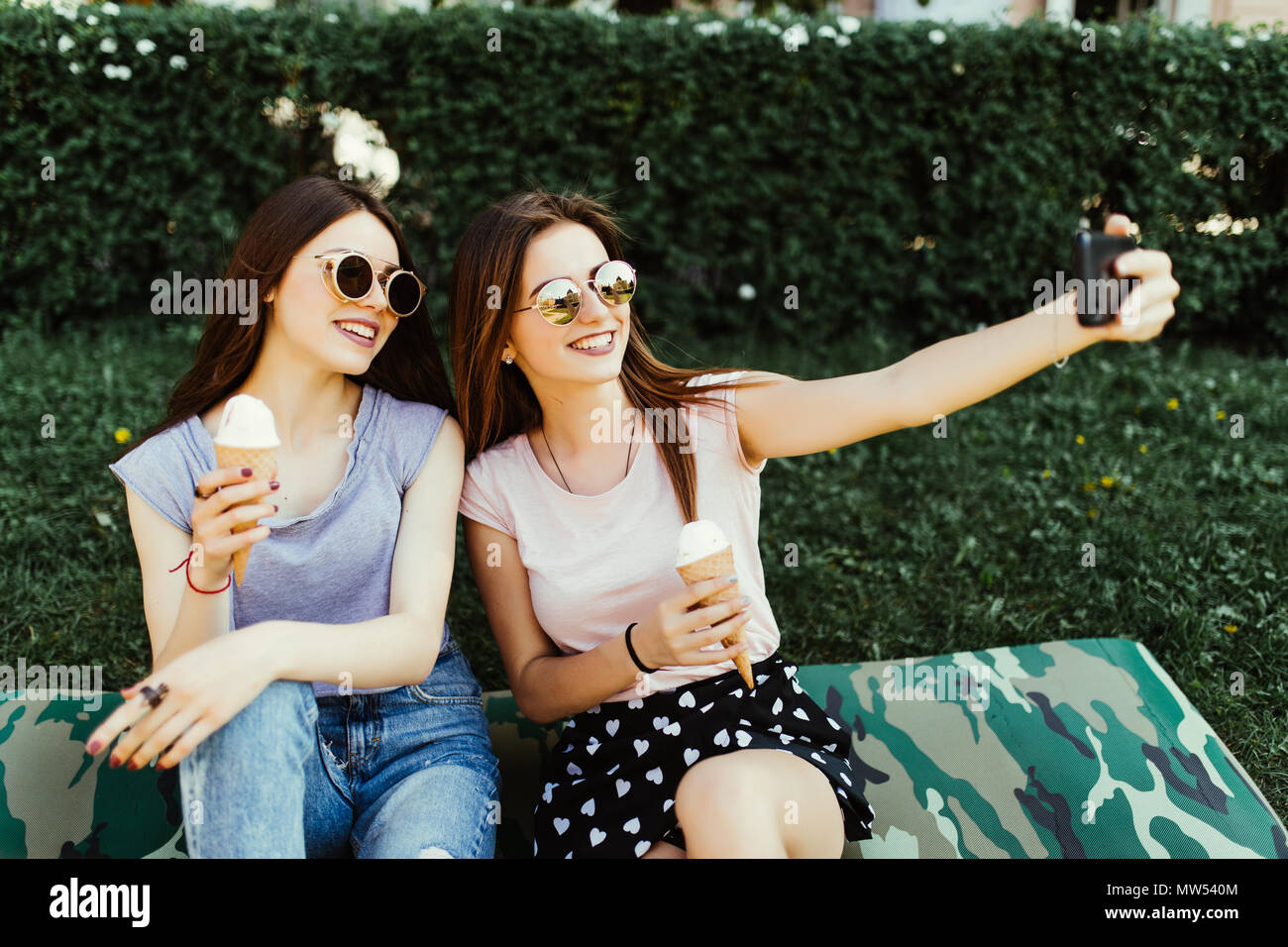 Portrait of two young women standing together eating ice cream and taking selfie photo on camera in summer street. Stock Photo