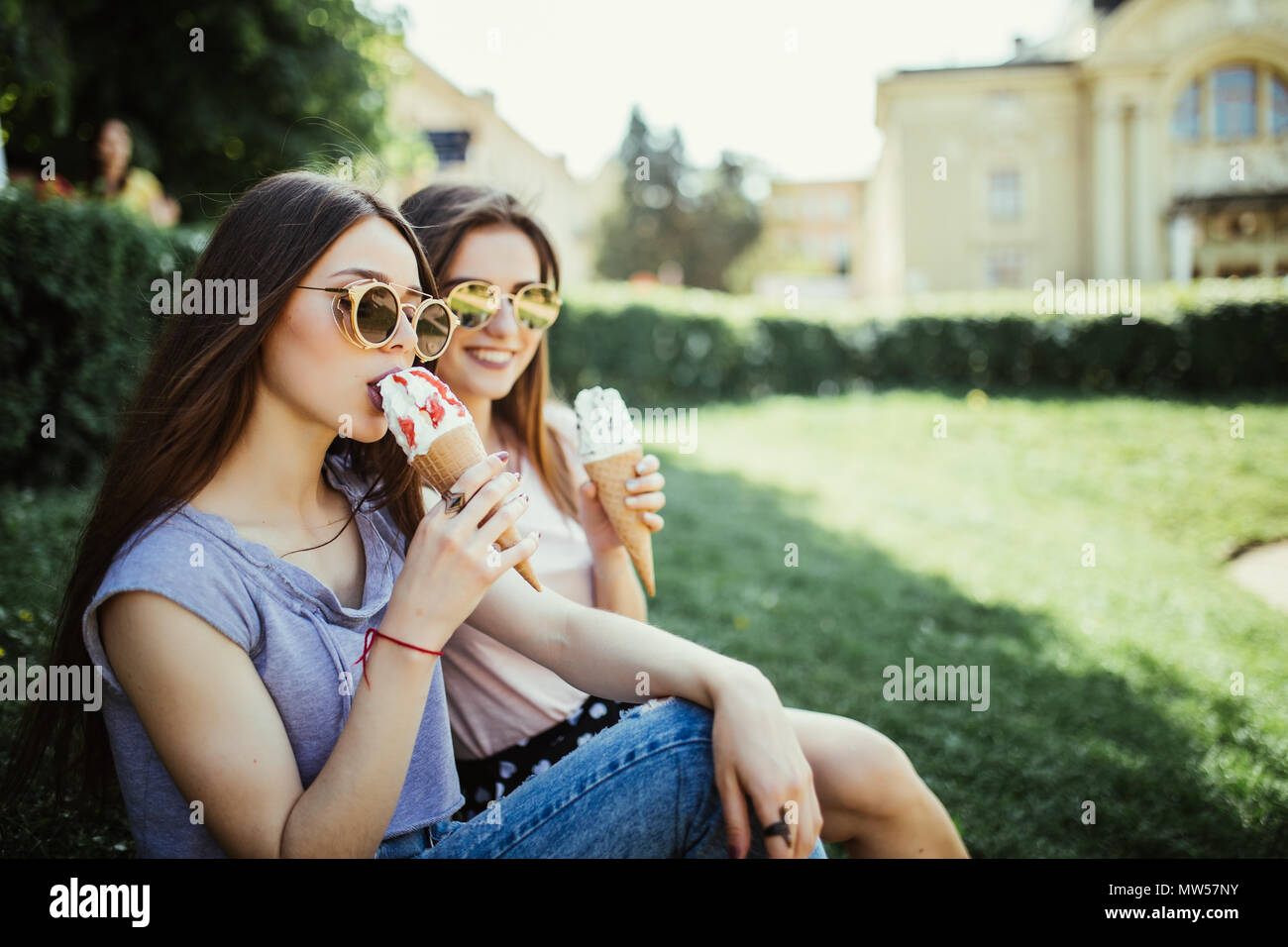 Young two women friends eat ice cream sitting on the grass in city streets - Stock Image