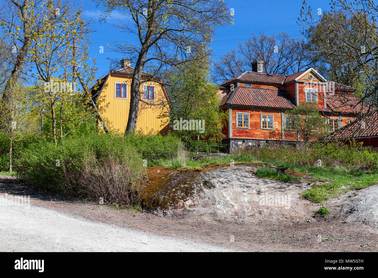 Swedish rural landscape, colorful old wooden houses on green hill - Stock Image