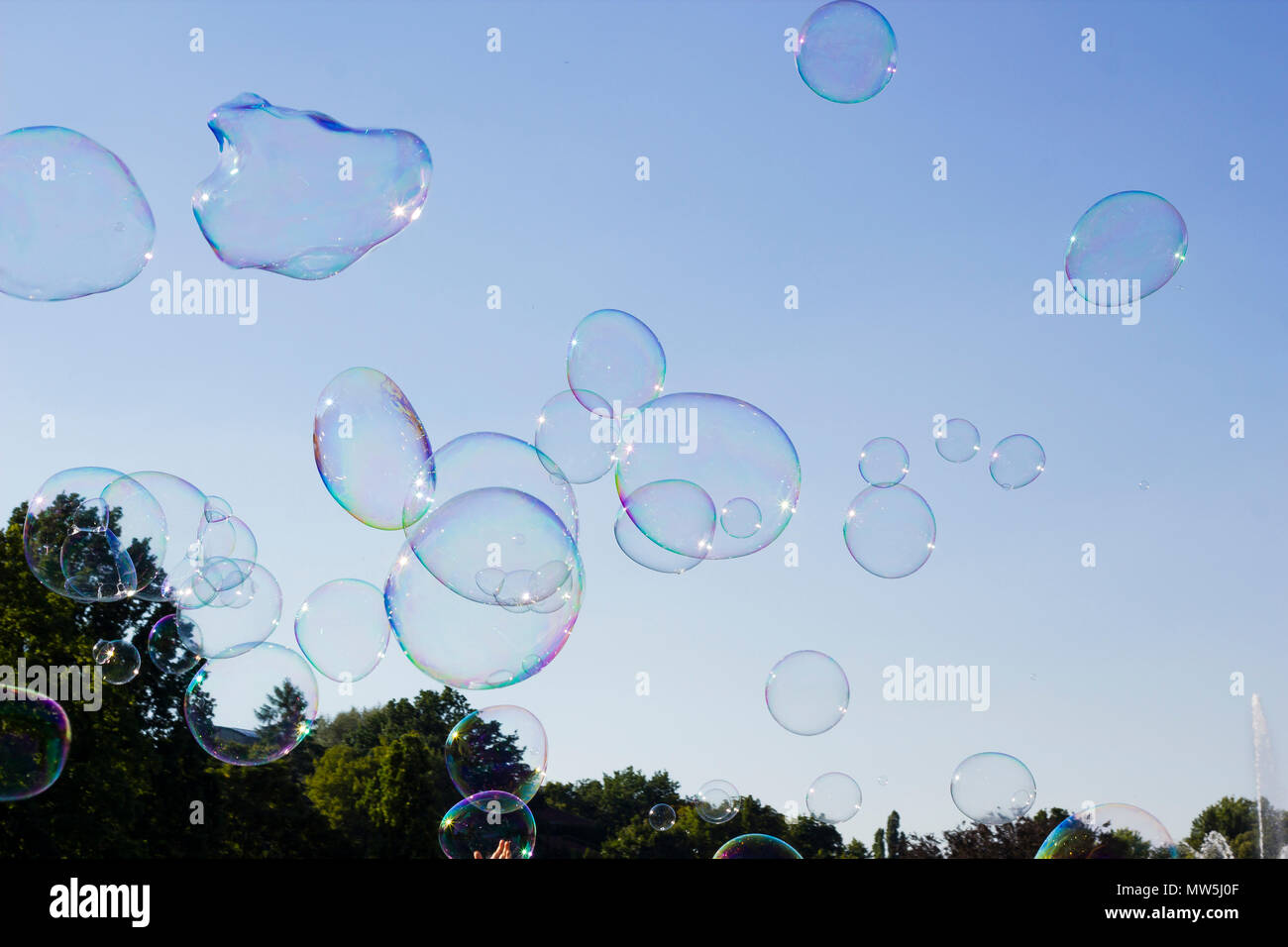Many large soap bubbles flying in air against blue sky, sunny summer day in city - Stock Image