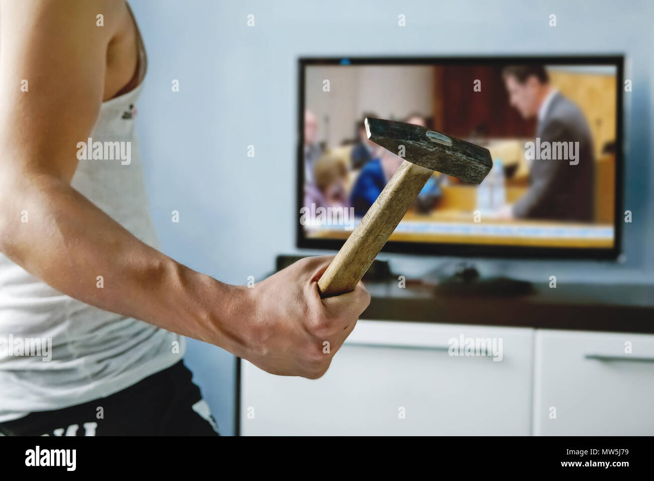 A psychopath wants to crash the TV with a hammer. fake news report. Man breaks TV screen. Fatigue from bad news. The evil guy is watching political ne Stock Photo