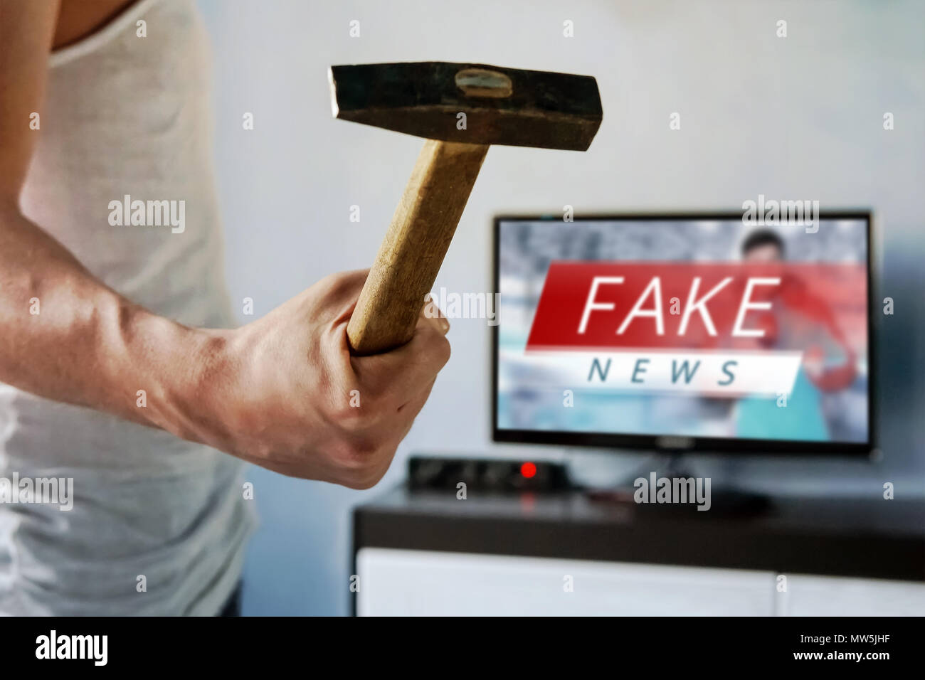 man wants to break the TV. guy swung a hammer at the screen. . Fake news on the TV screen, HOAX concept. News report with false news. Truth misreprese Stock Photo