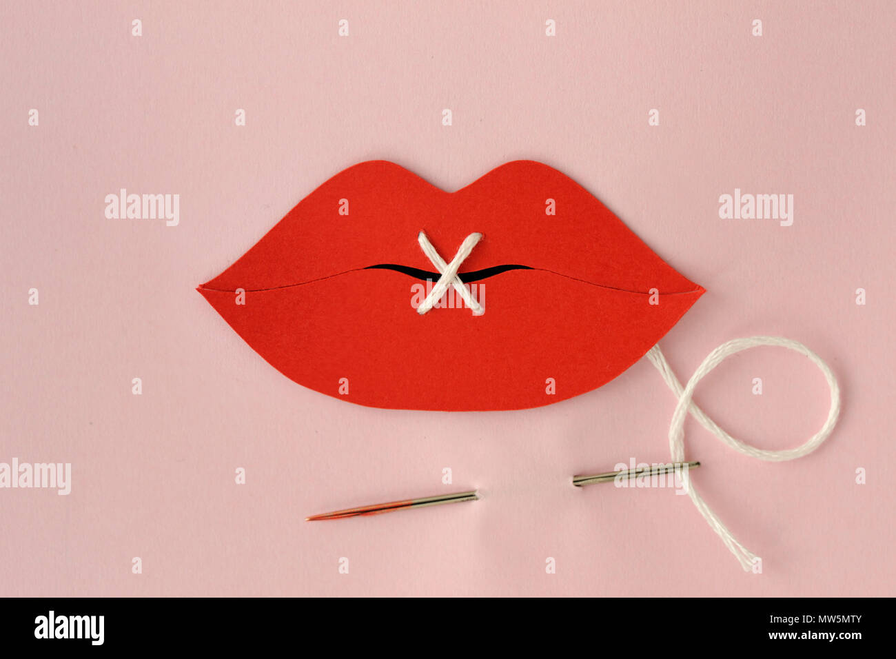 Paper lips cut-out sewn with white thread - Violence against women concept - Stock Image