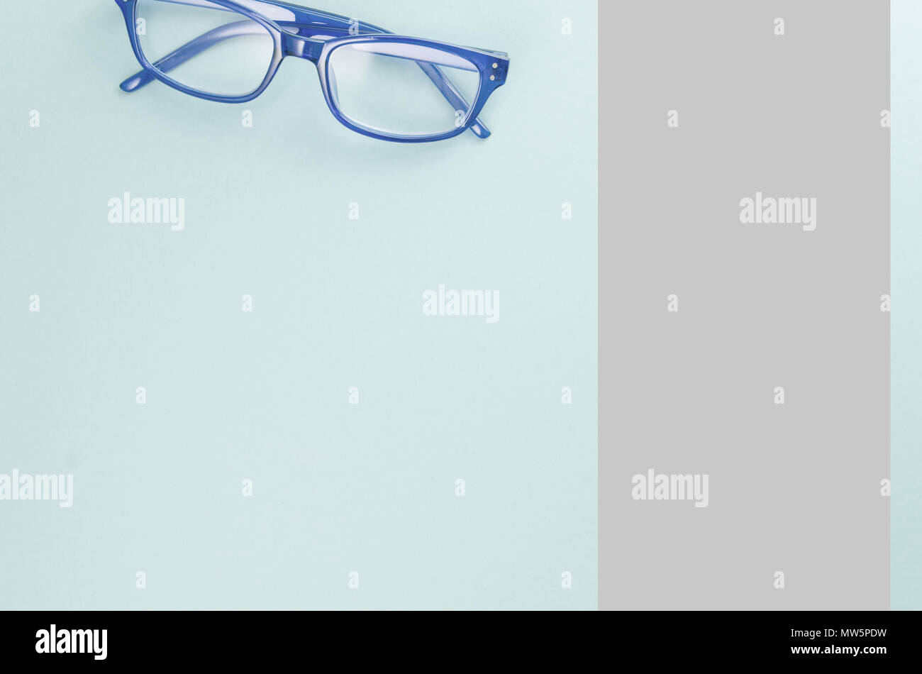 pair of blue frame eyeglasses on a light blue surface - directly above - Stock Image