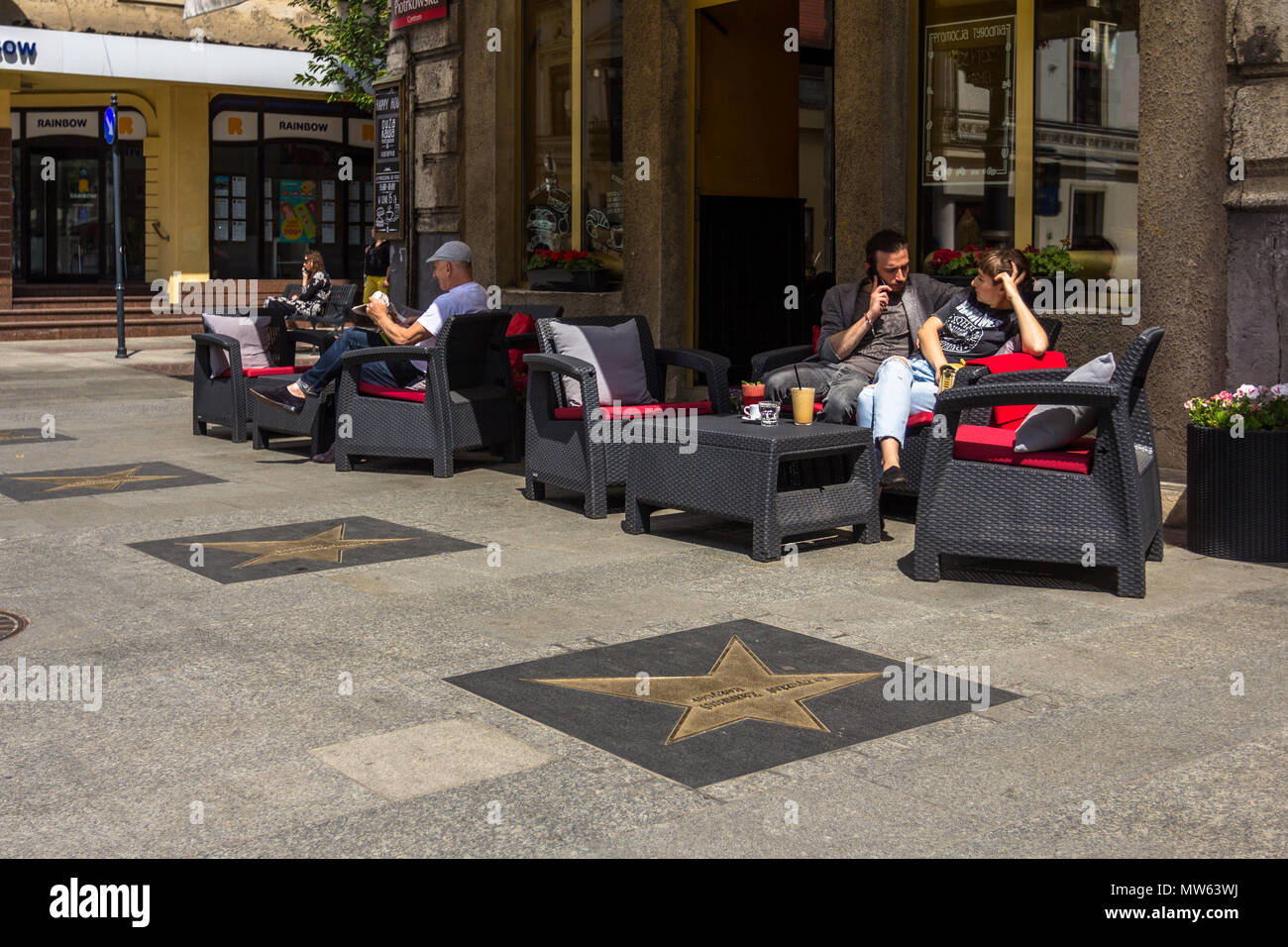People sitting on chairs outside cafe restaurant in Piotrkowska Street in Łódź, Łódzkie, Poland, showing stars from Łódź Avenue of Fame - Stock Image