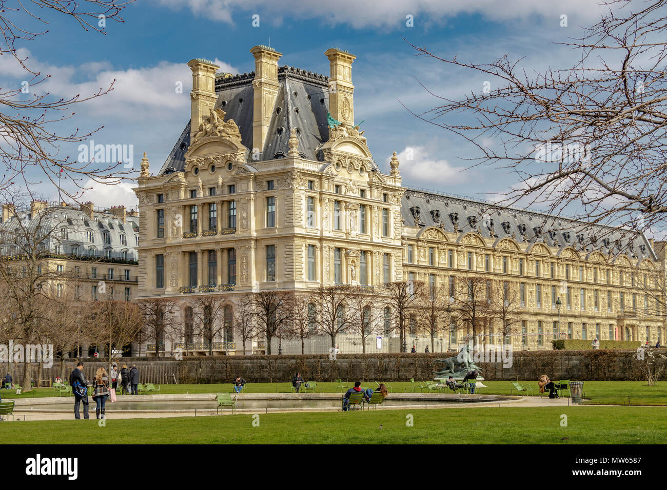 People relaxing in the winter sunshine in the Jardin des Tuileries with  Pavillon de Marsan part of the The Louvre museum in the background ,Paris Stock Photo