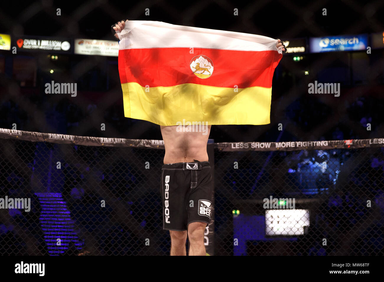 Ossetian MMA fighter Batraz Agnaev holds up the flag of the Republic of North Ossetia-Alania (often North Ossetia) after a win at a Mixed Martial Arts event in Manchester, UK. North Ossetia-Alania is a federal subject of Russia. - Stock Image