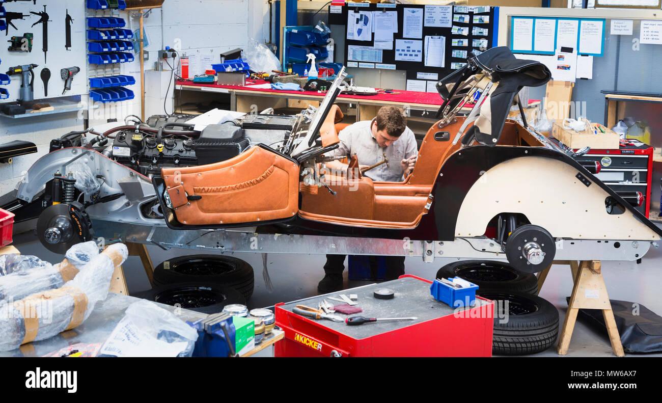 Interior of the Morgan Motor Car Company at Malvern Link, Malvern, Worcestershire, England, United Kingdom.  Engineer working on cars.  Morgan cars ar - Stock Image