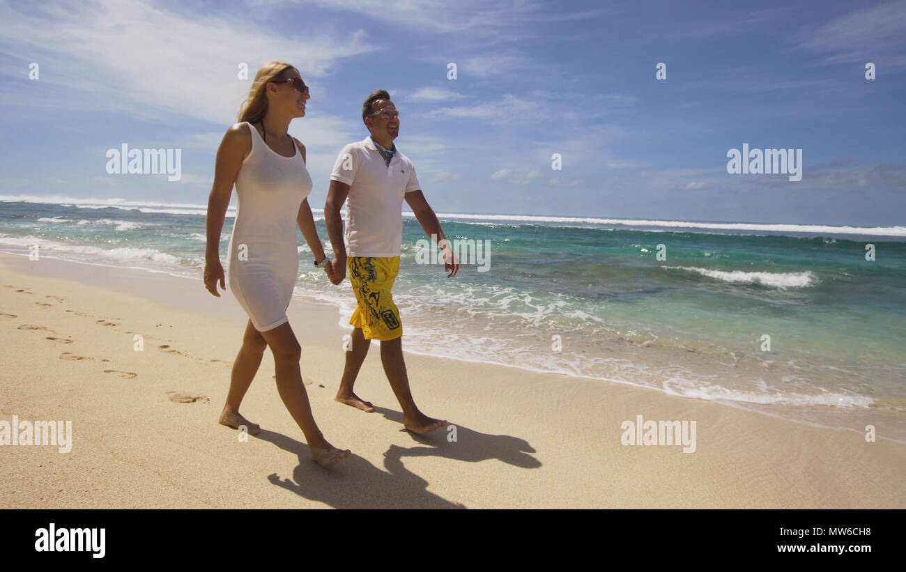 Beautiful Couple holding hands walking along the beach. Relationships, Beach, couple on romantic travel honeymoon vacation summer holidays romance. Young happy lovers. Travel concept. Bali. - Stock Image