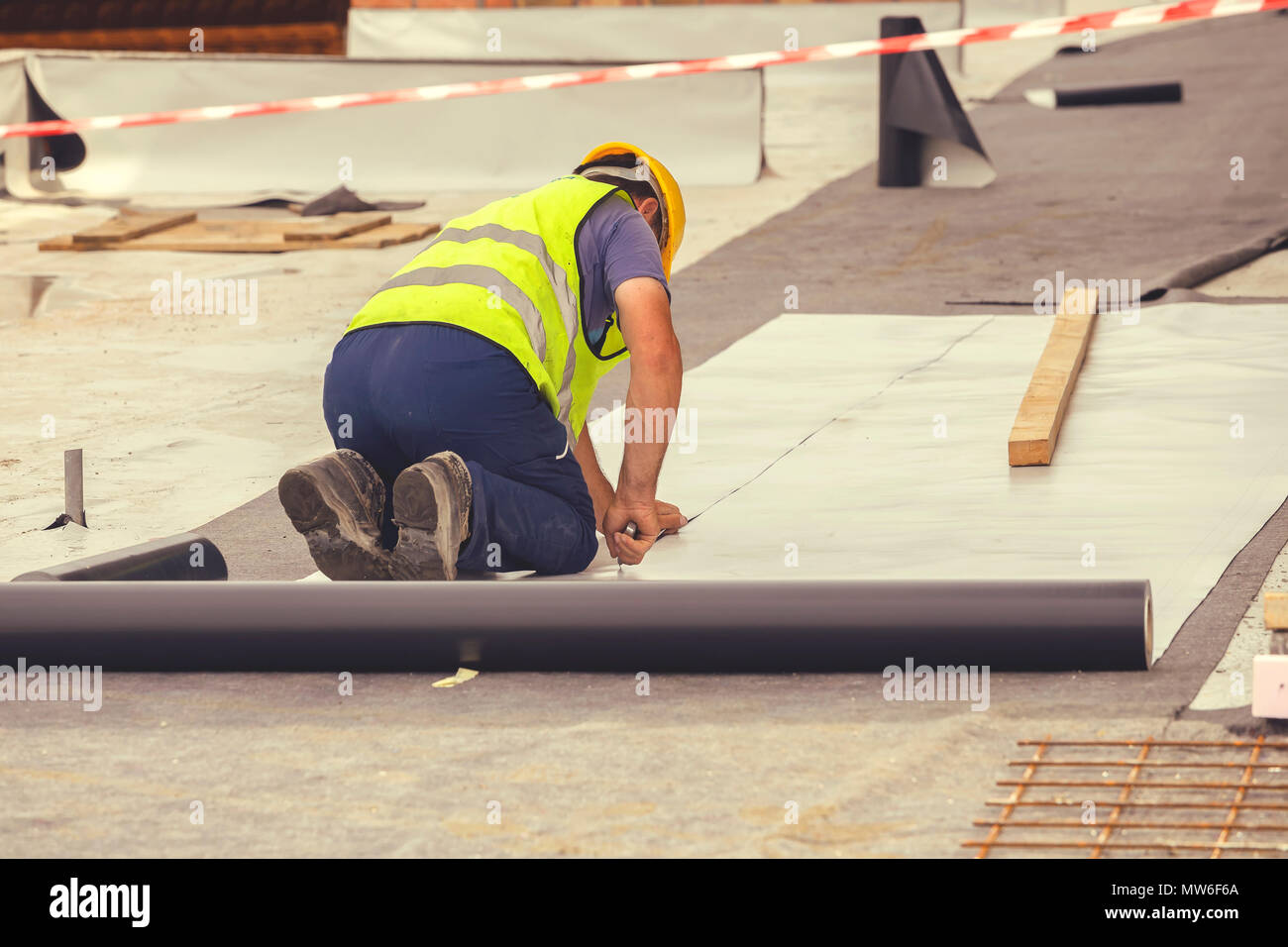 Waterproofing and insulation at construction site, waterproofing membrane preventing water penetration. Exterior vapor barrier for foundations and bas - Stock Image