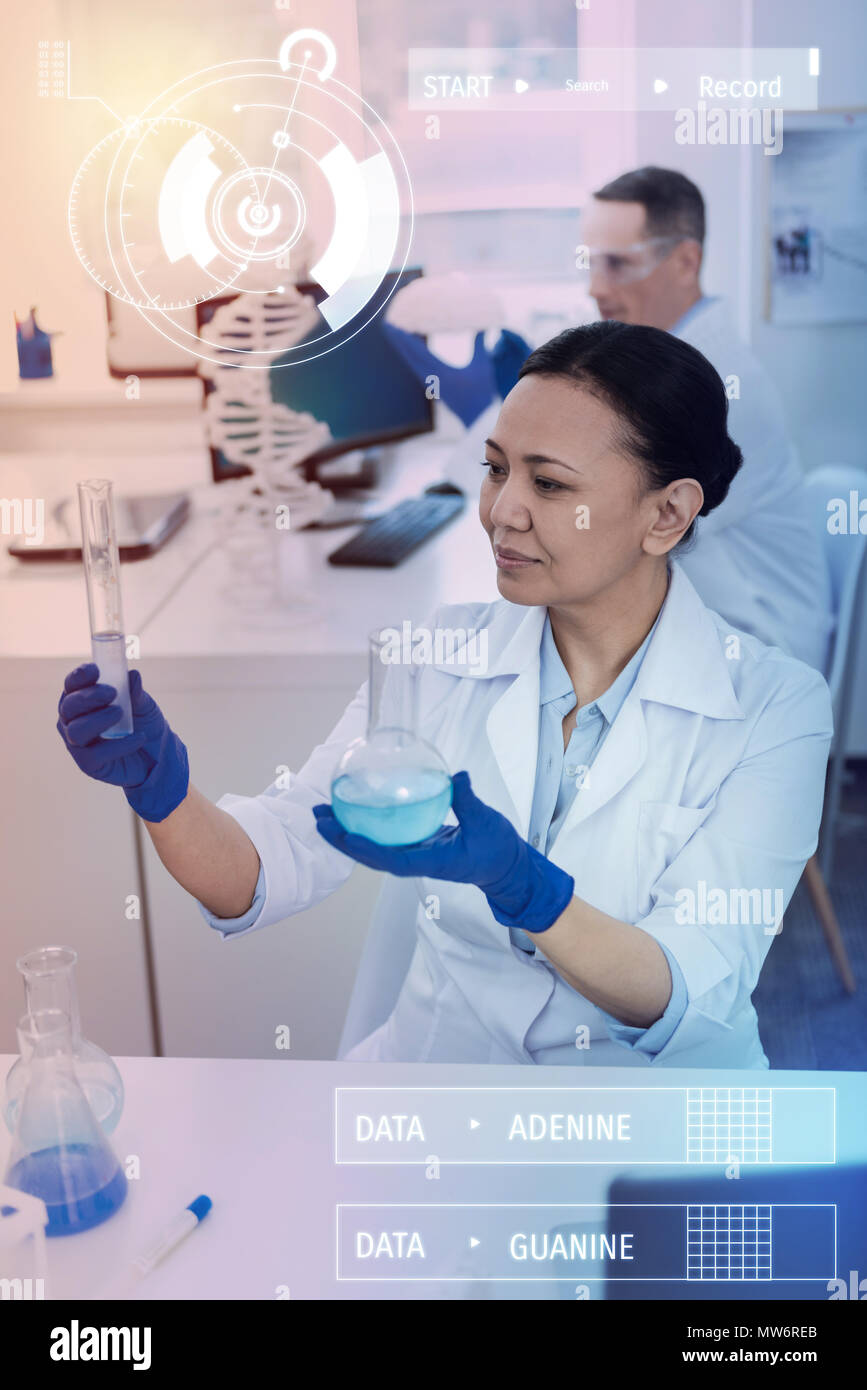 Careful chemist holding two bottles and looking at them - Stock Image