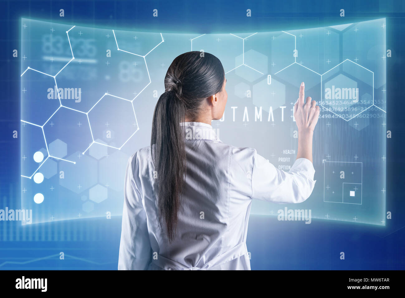 Progressive biologist touching a transparent screen while working - Stock Image