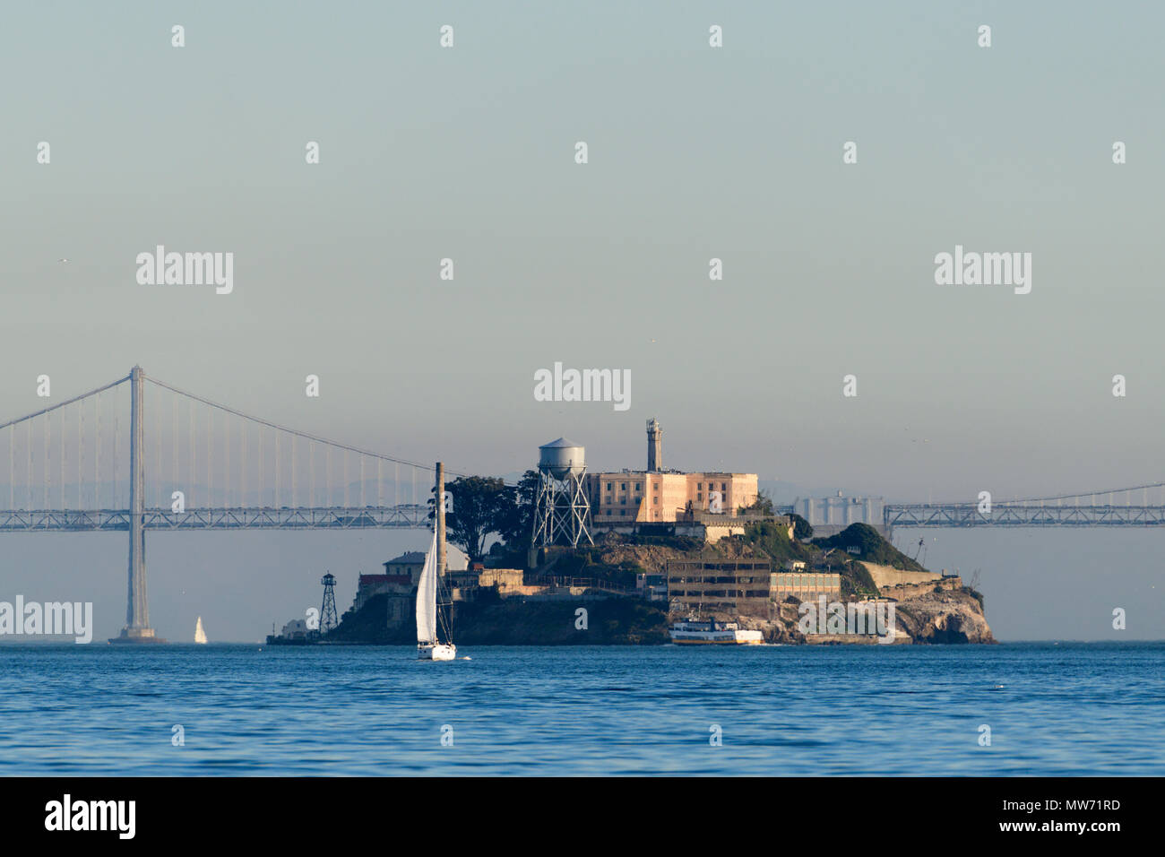 Alcatraz island with the new Bay Bridge in the background and sailboat on the water as seen from the water in San Francisco Bay - Stock Image