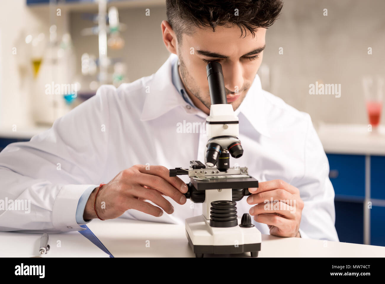Young lab technician in white coat looking into the microscope in laboratory - Stock Image