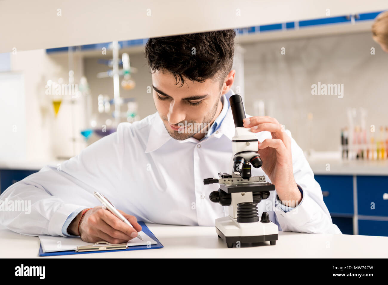 Young lab technician in white coat taking notes and using microscope in laboratory - Stock Image