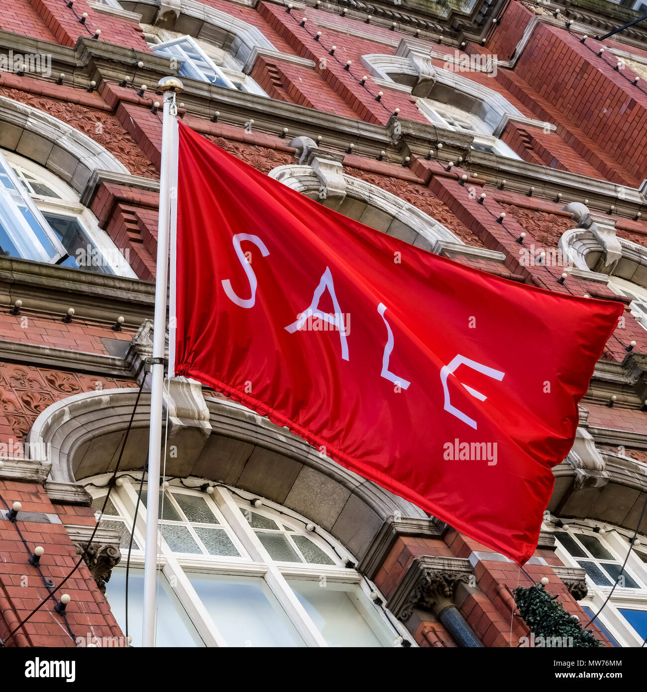Shopping,sale red flag flying at Arnotts Department Store,brownstone building facade,on Henry Street. Dublin,Ireland. Close up,low angle view. - Stock Image