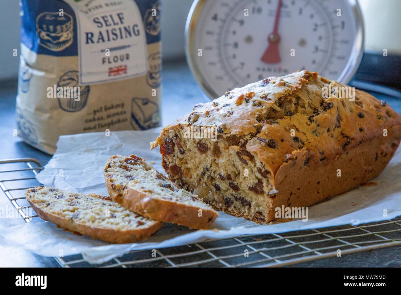 A reshly baked fruit tea loaf on a cooling rack. - Stock Image