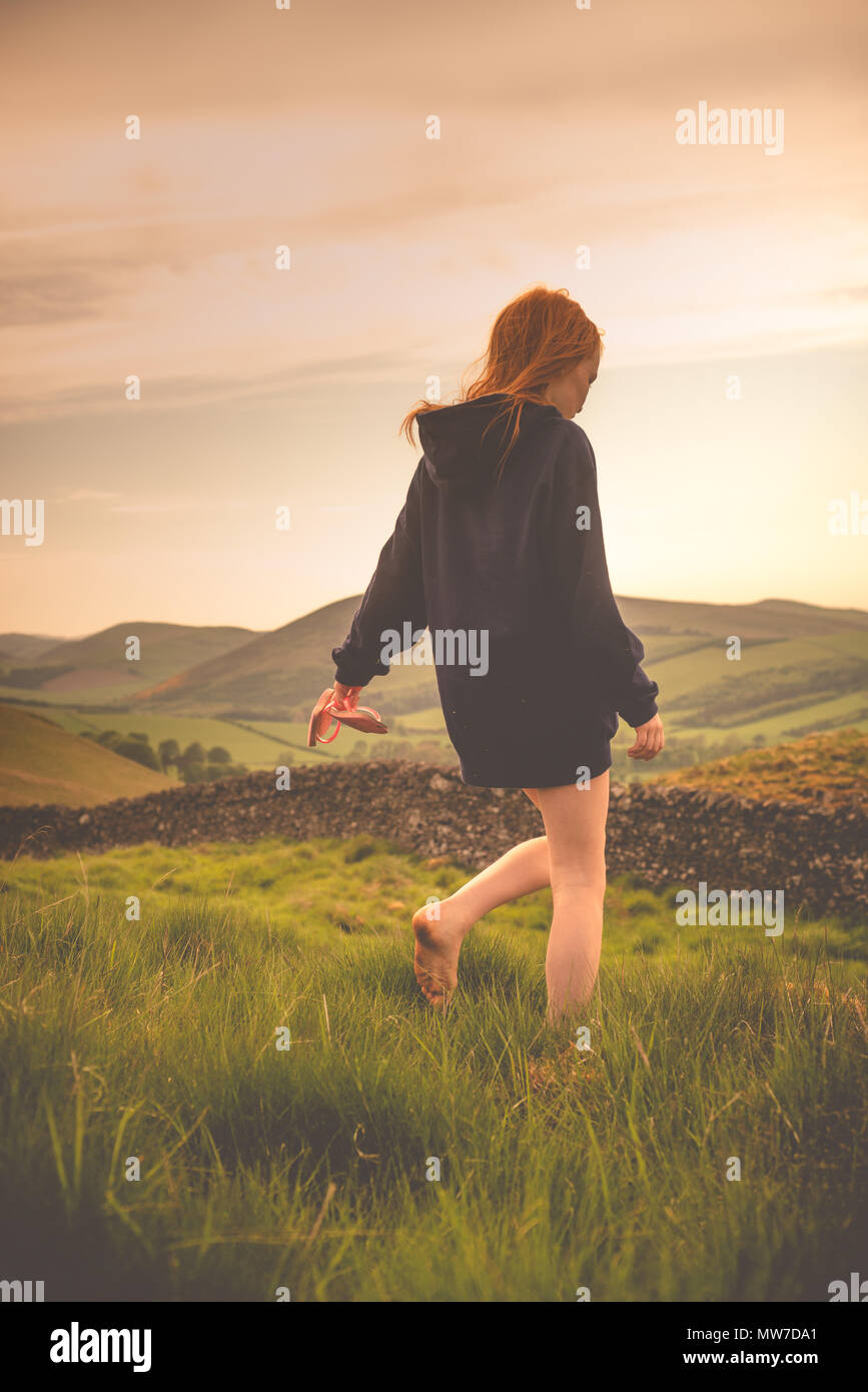 A Girl With Ginger Hair Walks with Bare Feet in a Field in the Scotttish Countryside - Stock Image
