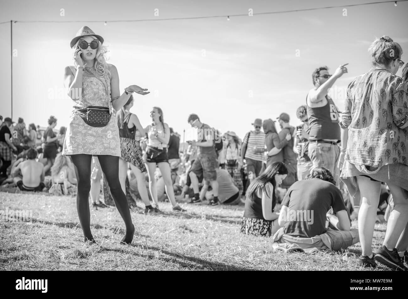 A festival goer speaks on her phone at the Glastonbury Festival 2015 - Stock Image