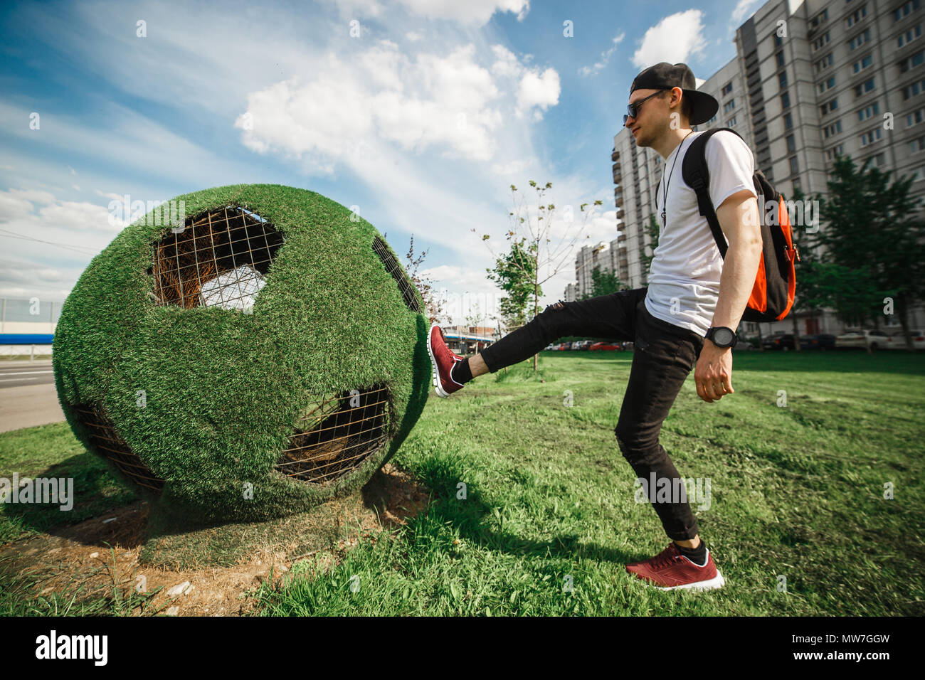 Saint-Petersburg, Russia, 21.05.2018. Stylish handsome man tourist is kicking the ball soccer ball of grass. Russian World cup concept. - Stock Image